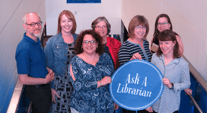 Hazy Library Staff hold a sign that reads: Ask a Librarian